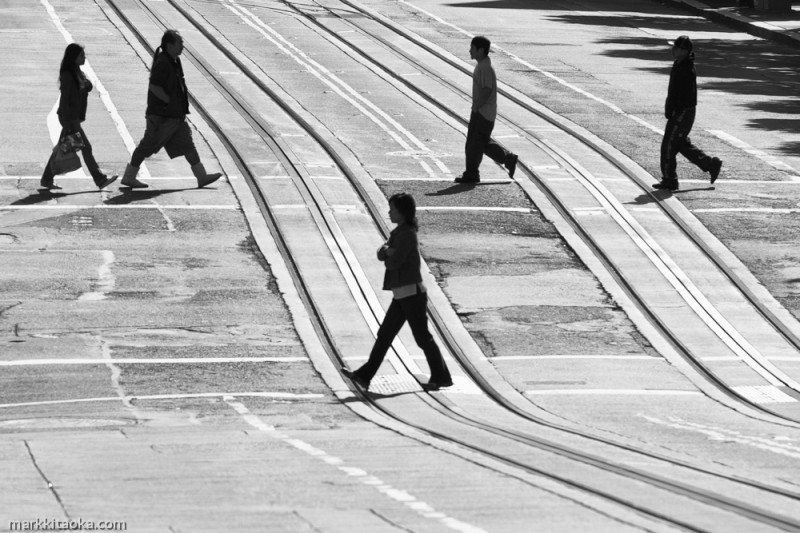 """Intersection"" For this image I went into San Francisco one Saturday morning and waited as I watched people crossing California Avenue on Kearny Street. I waited until I observed these five people walking and snapped the image as they were in this formation. It was almost noon so I knew the subjects would be silhouetted, but that was my plan for this shot. Light, expression, environment."