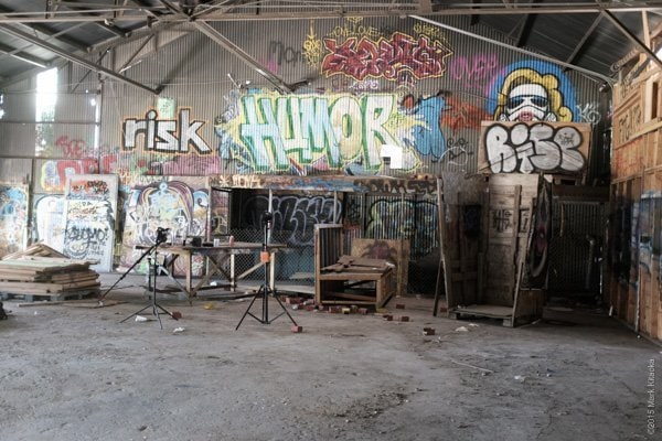 An extremely cool graffiti barn as seen with natural ambient light. Because this was indoors I used two of the bare bulb 360 units, one a Godox the other a Streaklight. The key light was placed above the wooden box to the right where the talent posed. I used a gridded cone reflector for the key light. The second 360 was place about 30 feet away from the box pointed toward the Humor word but pointed at the ground. I wanted some illumination to the background and to cast shadows on the floor.